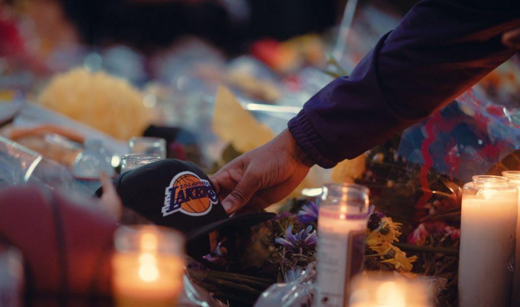 Fan gingerly placing a Lakers hat remembering Kobe at his memorial